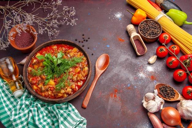 暗い背景にさまざまな調味料とトマトを使ったおいしい調理済み野菜ソースミールの上面図ソースミールディッシュフード
