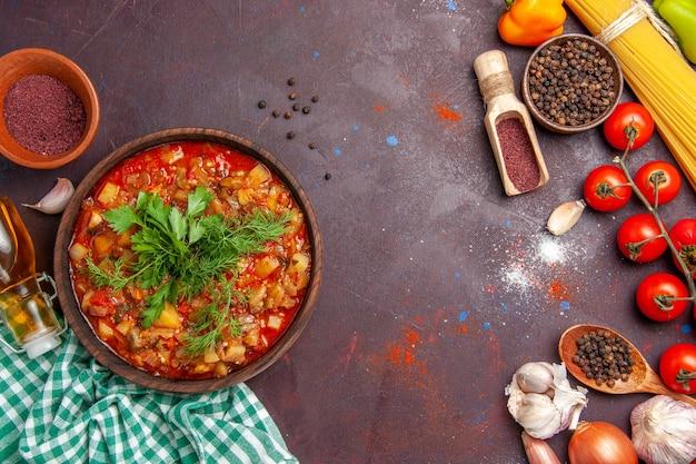 Вид сверху вкусной приготовленной овощной еды в соусе с разными приправами на темно-фиолетовом фоне