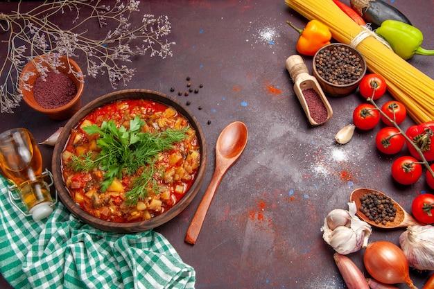 Vista dall'alto gustoso pasto di salsa di verdure cotte con diversi condimenti e pomodori su sfondo scuro salsa pasto piatto cibo