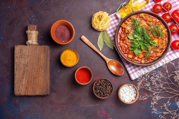 Вид сверху вкусные приготовленные овощные блюда в соусе с помидорами и приправами на темном фоне ужин соус еда блюдо еда