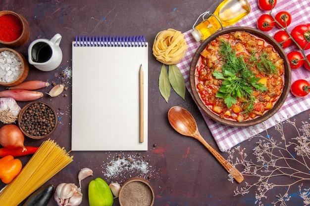 暗い背景にトマトと調味料を使ったおいしい調理野菜ソースミールの上面図ソースミールディッシュフード