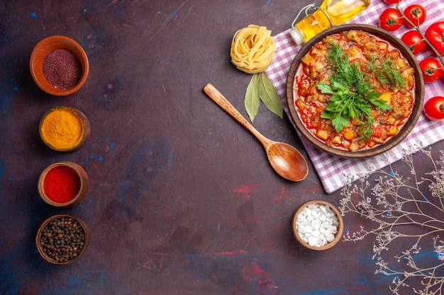 Top view tasty cooked vegetables sauce meal with tomatoes and seasonings on a dark background meal dinner sauce food dish