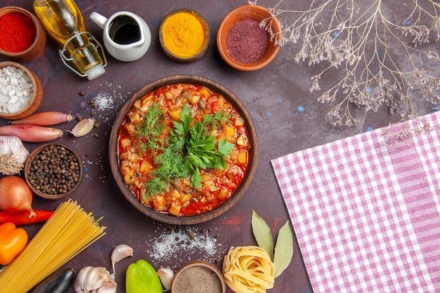 トップビューソースでスライスしたおいしい調理済み野菜と暗い背景のさまざまな調味料フードソーススープディナーミール