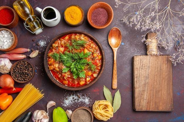Вид сверху вкусные приготовленные овощи, нарезанные соусом и приправами на темной поверхности, соус, суп, ужин, обед