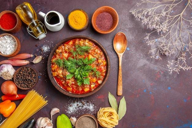 暗い背景にソースと調味料でスライスしたおいしい調理済み野菜の上面図ソーススープ食品夕食