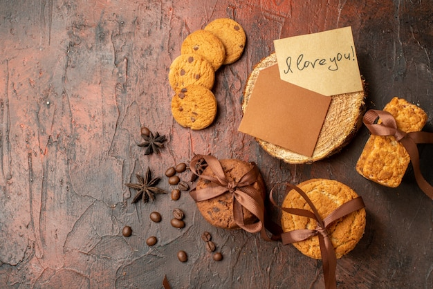 Top view tasty cookies tied with rope biscuits anises love letter on dark red table with
