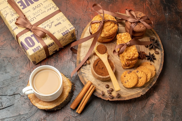 Top view tasty cookies tied with rope biscuits anises on wood board cup of coffee gift on dark red table