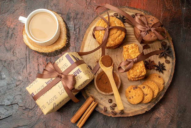 Top view tasty cookies tied with rope biscuits anises on wood board gift cup of coffee on dark red table