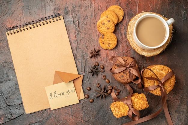 Вид сверху вкусное печенье, перевязанное веревкой, печенье, я люблю тебя, написано на липкой записке, чашка кофе, блокнот на столе