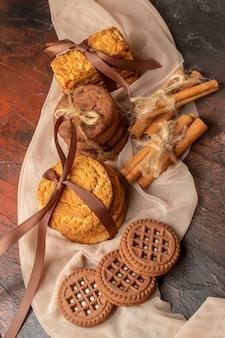 Вид сверху вкусного печенья, перевязанного веревкой, печенья в палочках корицы со сливками на темном столе