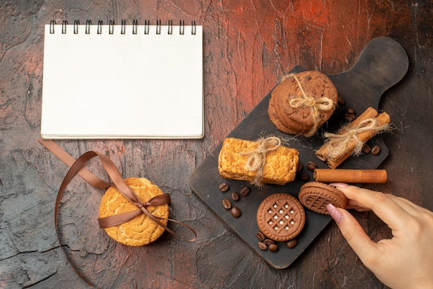 Top view tasty cookies tied with rope cinnamon sticks biscuits on wood serving board biscuit in female hand notepad on dark table