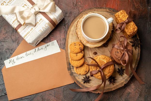 Вид сверху вкусного печенья, перевязанного веревкой, чашка кофе на деревянной доске, любовное письмо в подарочном конверте на столе