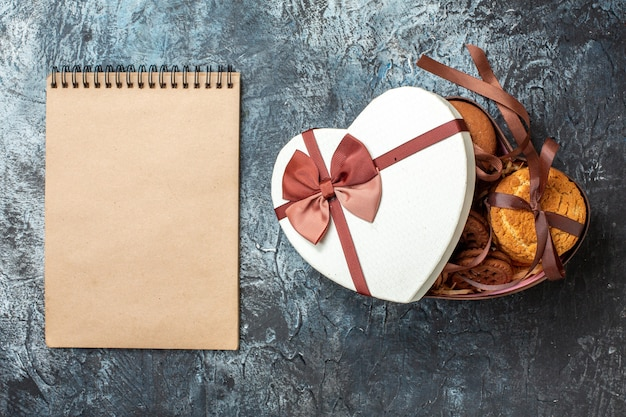 Top view tasty cookies tied with rope in heart shaped box with cover notepad on grey table