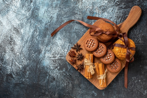 Top view tasty cookies tied with rope star anises cinnamon sticks on wood serving board on dark background