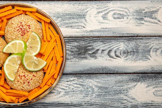 素朴な灰色の机の上のレモンスライスとラスクのおいしいクッキーの上面図ビスケットシュガーケーキパイ甘いクッキー