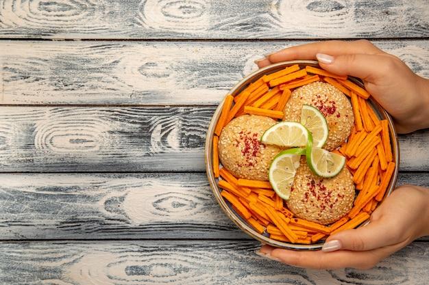 Вид сверху вкусное печенье с ломтиками лимона и сухариками на деревенском сером столе, печенье, сахарный торт, закуска, сладкое печенье