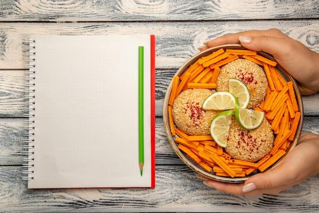 灰色の机の上のレモンスライスとラスクのトップビューおいしいクッキービスケットシュガーケーキスナック甘いクッキー