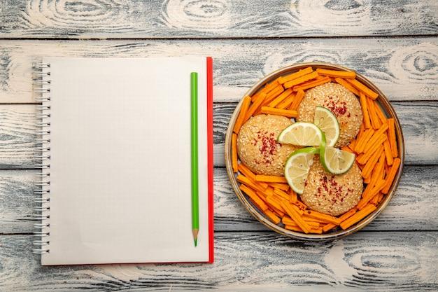 素朴な灰色の机の上のレモンスライスとラスクのトップビューおいしいクッキービスケットシュガーケーキスナック甘いクッキー