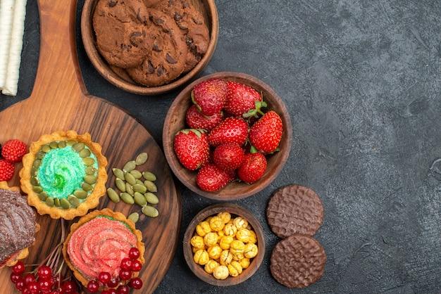 Вид сверху вкусные сливочные пирожные с печеньем и фруктами на темном столе, печенье сладкий десерт