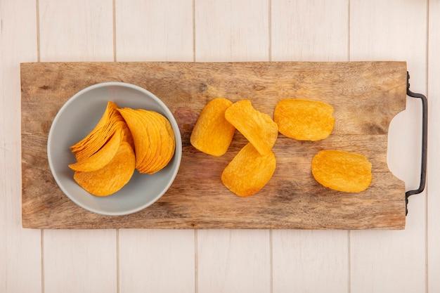 Vista dall'alto di gustose patatine croccanti su una ciotola su una tavola da cucina in legno su un tavolo in legno beige