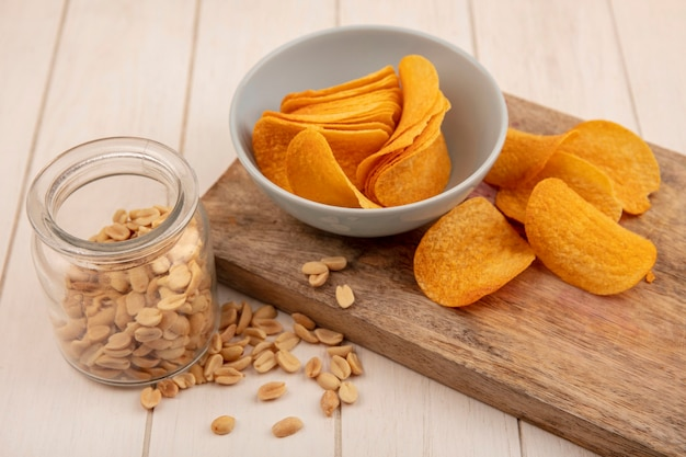 Top view of tasty crispy chips on a bowl on a wooden kitchen board with pine nuts on a glass jar on a beige wooden table