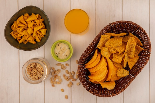 Top view of tasty crispy chips on a bucket with a glass of orange juice with sauce with pine nuts on a glass jar on a beige wooden table