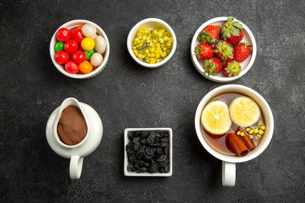 Top view tasty dessert a cup of appetizing herbal tea next to the bowls of chocolate cream colorful candies herbs and strawberries on the dark table