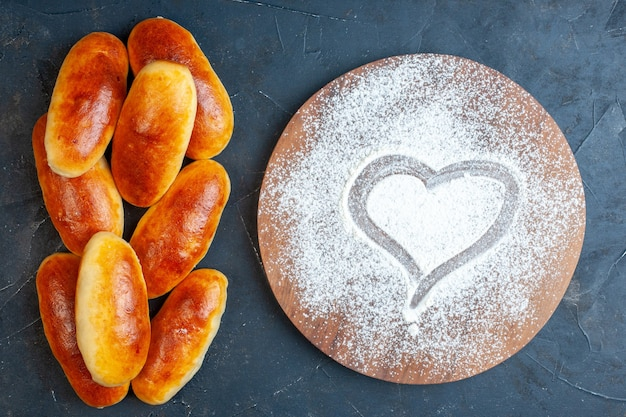 Top view tasty dinner rolls heart imprint in powdered sugar on wood board on table