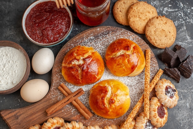 Top view tasty dinner rolls on wood serving board eggs cookies biscuits with jam on dark table