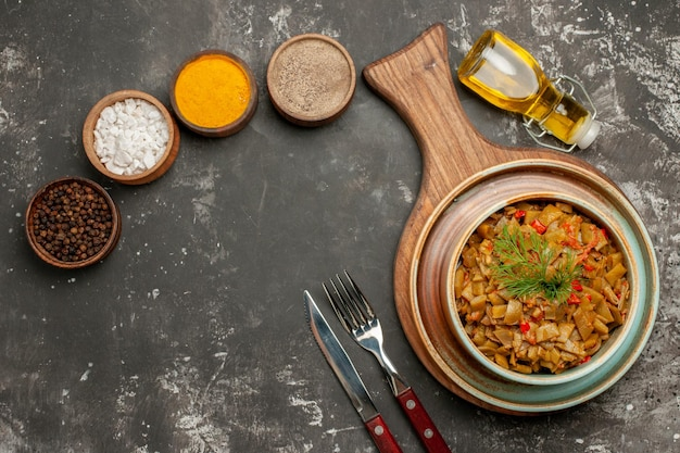 Вид сверху вкусное блюдо зеленая фасоль с помидорами на доске рядом с вилкой, ножом, бутылкой масляных помидоров с цветоножками и четырьмя мисками разноцветных специй на темном столе