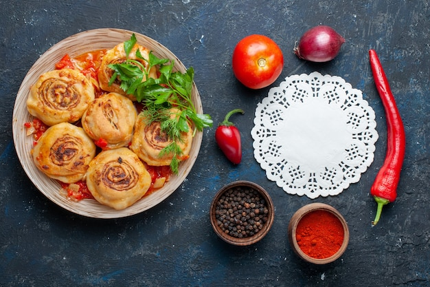 Вид сверху вкусной муки из теста с мясом внутри тарелки вместе со свежими овощами, такими как лук, помидоры на темно-сером столе, еда, еда, мясо, овощи