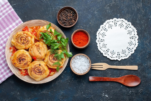 プレートの内側に肉が入ったおいしい生地の食事と、暗い机の上の調味料スプーンの上面図食品食事肉野菜