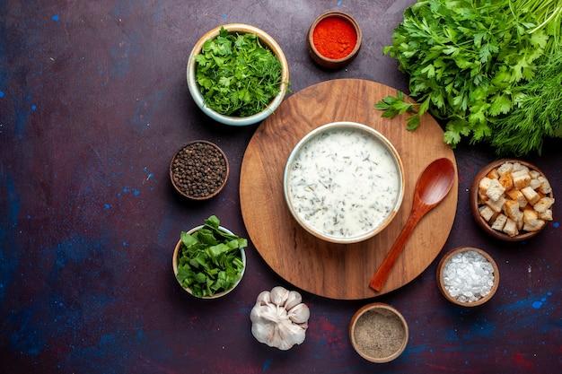 Вид сверху вкусная довга со свежей зеленью, сухариками и приправами на темно-фиолетовом столе, еда суп овощной