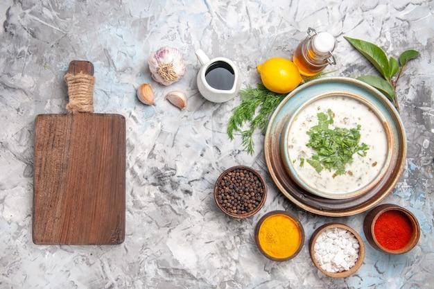 Vista dall'alto gustosa zuppa di yogurt dovga con verdure sul latte da tavola bianco chiaro piatto di zuppa di latte