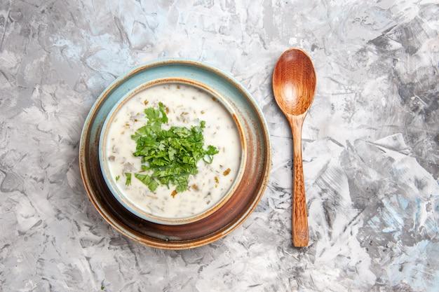上面図白いテーブルの乳製品のミルクスープ皿に緑のおいしいdovgaヨーグルトスープ
