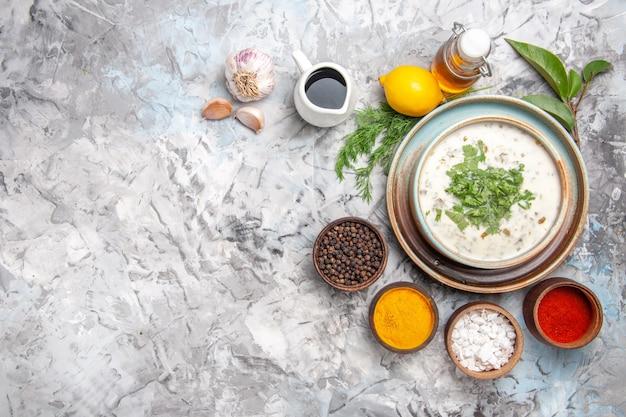 上面図白いテーブルのミルク皿の乳製品に緑のおいしいdovgaヨーグルトスープ