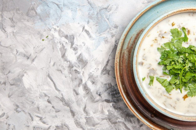 Top view tasty dovga yogurt soup with greens on white floor milk soup meal dish