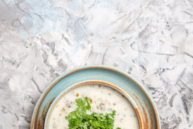 Top view tasty dovga yogurt soup with greens on white table milk meal dish