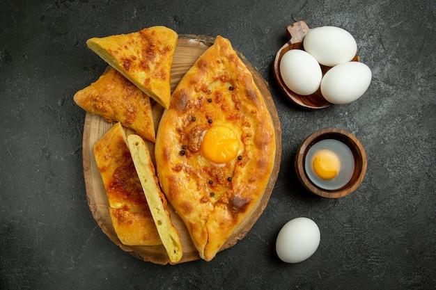 Вид сверху вкусный яичный хлеб, запеченный со свежими яйцами на сером фоне, хлеб, булочка, тесто, еда, завтрак