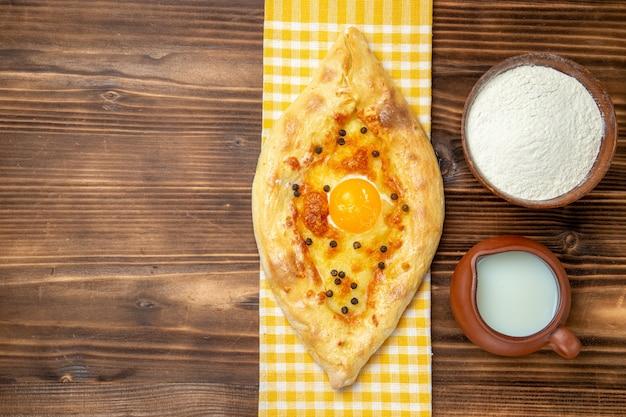 나무 책상 반죽에 우유와 함께 오븐에서 신선한 상위 뷰 맛있는 계란 빵 빵 빵 롤빵 계란