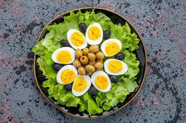 Vista dall'alto gustosa insalata di uova composta da insalata verde e olive su sfondo chiaro