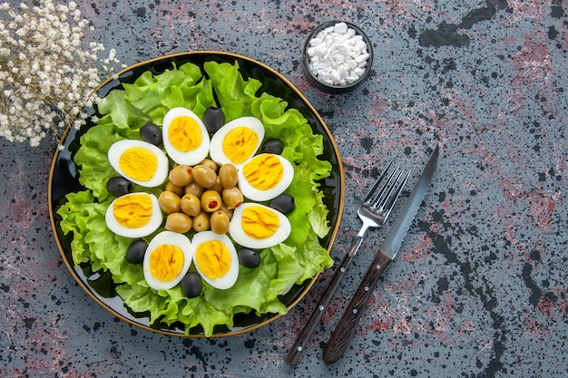 Top view tasty egg salad consists of green salad and olives on light background