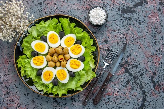 トップビューおいしいエッグサラダは、明るい背景にグリーンサラダとオリーブで構成されています