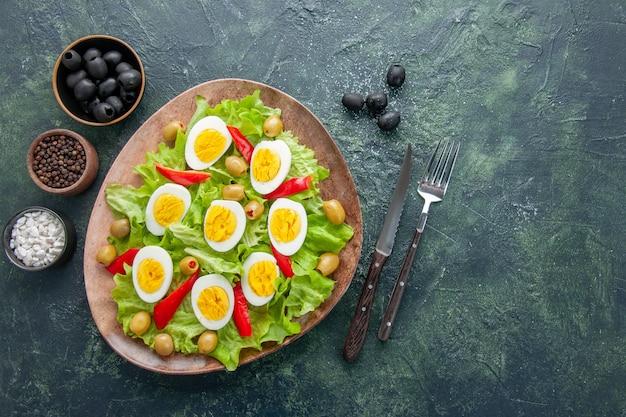 Вид сверху вкусный яичный салат с зеленым салатом, оливками и приправами на темном фоне