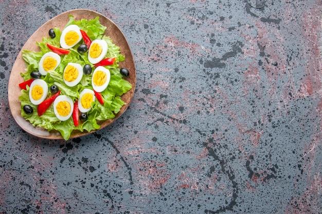Vista dall'alto gustosa insalata di uova con insalata verde e olive all'interno della piastra su sfondo chiaro
