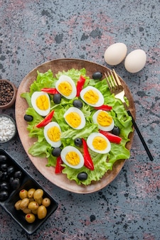 Top view tasty egg salad with green salad and olives on light background