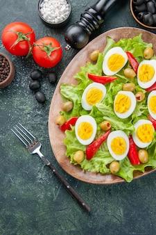 Vista dall'alto gustosa insalata di uova con insalata verde olive e condimenti su sfondo scuro