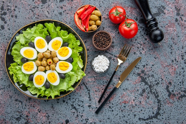 Top view tasty egg salad with seasonings and olives on light background