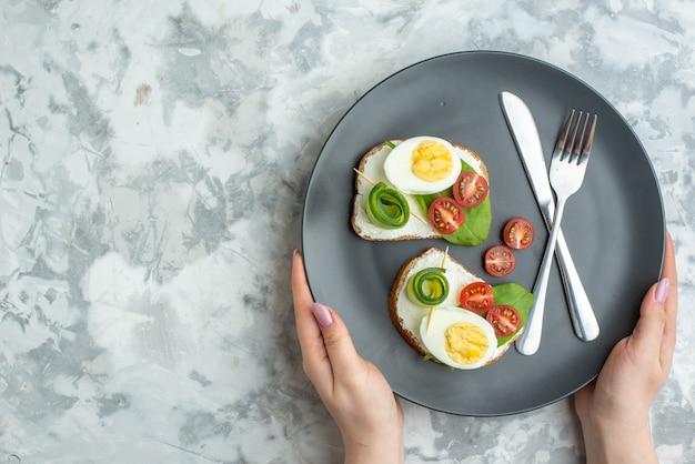 上面図プレートの内側にナイフとフォークが付いたおいしい卵サンドイッチ白い背景サンドイッチダイエットランチ食品健康ハンバーガーパンミール