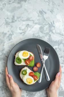 上面図おいしい卵サンドイッチとナイフとフォークの内側プレート白い背景サンドイッチダイエットランチトーストフードハンバーガーパンミール
